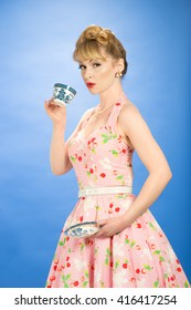Pin up girl drinking from vintage teacup and saucer