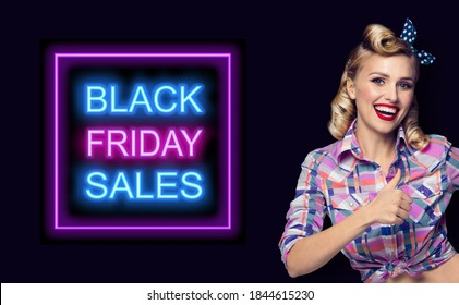 Pin up girl. Excited happy pinup woman showing thumb up gesture or like sign. Retro fashion and vintage concept. Dark background. Black Friday sales neon light sign.