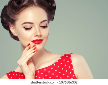 Pin up girl vintage. Beautiful woman pinup style portrait in retro dress and makeup, manicure nails hands, red lipstick and polka dot dress. Studio shot.