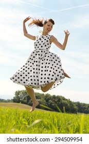 Pin up Girl with white petticoat dress is jumping in the meadow
