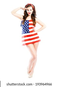 Pin up girl wrapped in american flag saluting isolated white