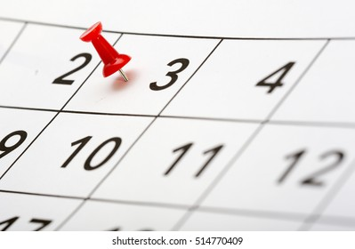 Pin on the date. The third day of the month is marked with a red thumbtack. Focus point on the red pin.