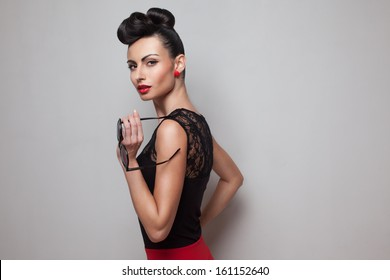 Pin Up style woman holding round sunglasses posing in red skirt. Red lips. Updo, twisted high bun. top knot
