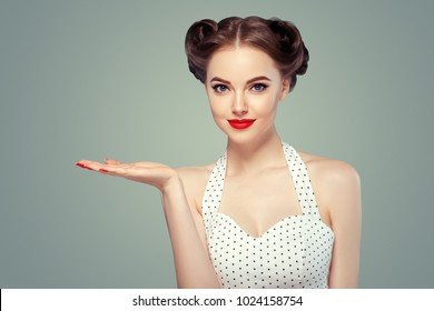 Pin up woman portrait. Beautiful retro female in polka dot dress with red lips and manicure nails and old fshion hairstyle hand pointing to side