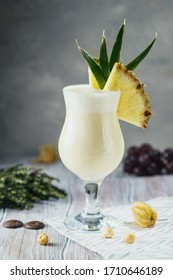 Pina Colada cocktail with decorations on craft light background with berries, nuts and greens