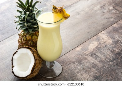 Pina colada cocktail on wooden background.