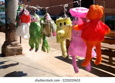 Pinatas funny creatures hand made, in colorful paper, by people hanging in mexican village street.