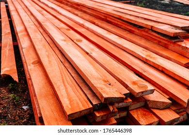 pine boards painted with red stain, lumber for construction are lying on the ground, long floor boards are stacked