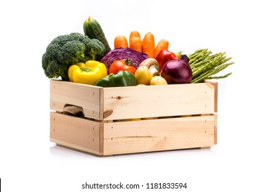 Pine box full of colorful fresh vegetables on a white background, ideal for a balanced diet, contains broccoli, cucumber, onion, asparagus, peppers, carrots, and potatoes