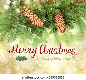 Pine branch with cones border with lights bokeh over golden blurred bokeh background with merry christmas greetings