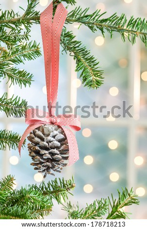 Pine Cone Christmas ornament hung from a Christmas tree with lights in the background. Shot with copy space.