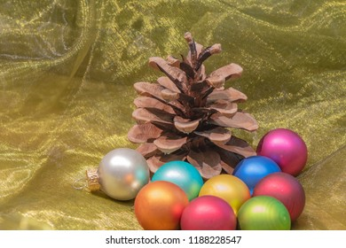 A pine cone and colorful Christmas tree balls on a colored towel.