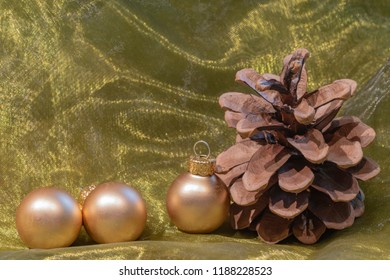 A pine cone and golden Christmas tree balls on a colored towel.