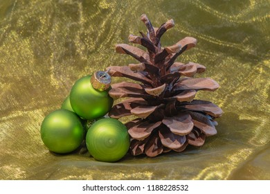 A pine cone and green Christmas tree balls on a colored towel.