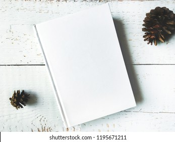 Pine cones, christmas winter mock up with book cover.Greetings card new year book mockup with christmas decoration. Christmas pine cones over white wooden background flat lay top view mock-up.