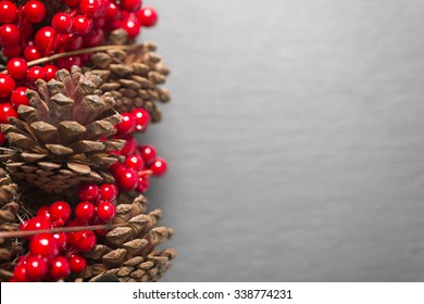 Kiefernkonserven und rote Holly-Beeren auf dunkler Schieferoberfläche
