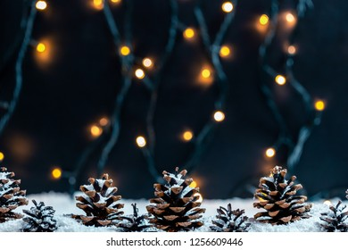 Pine Cones in snow on a blurred background of bokeh garland