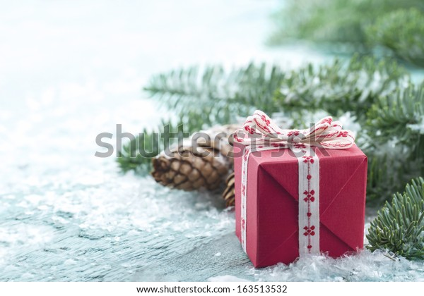 Pine cones, Xmas present and green spruce tree branches with snow in a decorative rustic Christmas setting on vintage light blue wooden background
