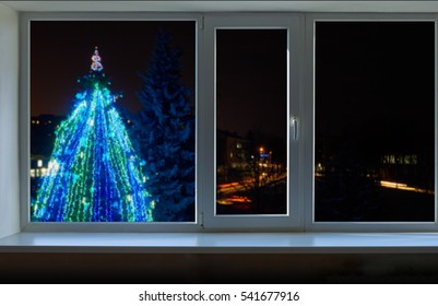 Pine decorated with garlands of different colors outside the window at night