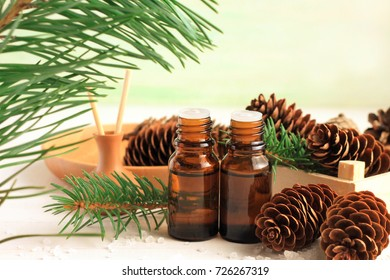 Pine essential oil bottles aromatherapy set, green needles fir tree branch, spruce cones. Winter herbal spa