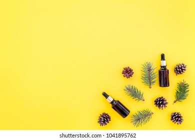 Pine essential oil in bottles on yellow background top view. Pattern with pine branch and cone copy space