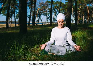 In a pine forest in summer, the girl sits in a lotus pose in white clothes and is practicing yoga kundalini closed eyes, relaxation