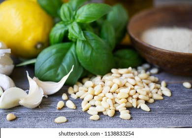 Pine nuts with basil and other pesto ingredients in the background.