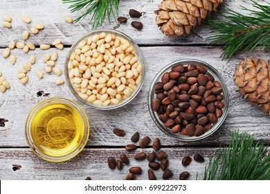 Pine nuts, oil and cedar cones on rustic wooden background top view. Organic and healthy superfood.