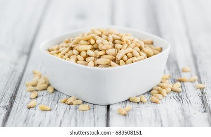 Pine Nuts on an old wooden table as detailed close-up shot (selective focus)