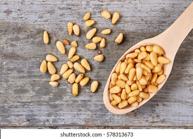 Pine nuts on wooden background. Discover the goodness of nuts.