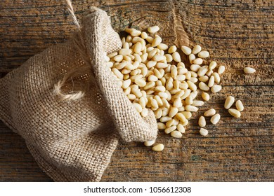 Pine nuts in small sack on wooden background