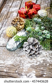 Pine and pinecone Christmas decorations on snowy wooden background