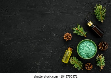 Pine spa cosmetics, products for skin care. Fir essential oil and green aromatic spa salt near branches and cones on black background top view copy space