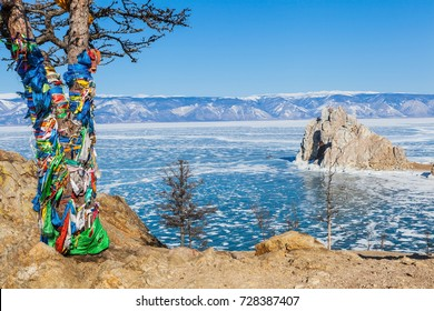 Pine Tree with colorful cloth to worship Shaman rock in frozen Baikal lake during winter with mountain range and blue sky in background,Siberia,Russia
