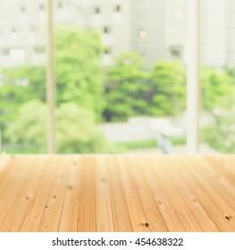 Pine wood floor beside big window room interiror with urban park garden view