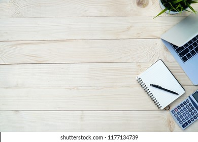Pine Wooden of desk table with workspace and empty blank notebook,computer laptop,calculator,pen,flower pot.Top view of tools for work office,flat lay.Copy space for text.
