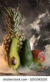 pineapple avocado and mango on marble slice with smoke