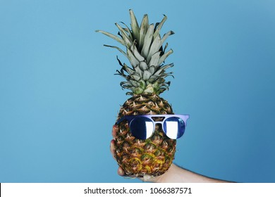 Pineapple with black sunglasses on blue background