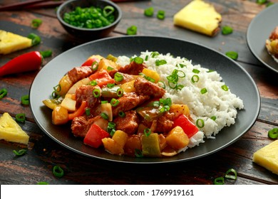 Pineapple and Chicken in sweet and sour sauce with bell pepper, rice and spring onion in black plate
