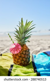 Pineapple cocktail on the beach resting on striped towel with blue sky background