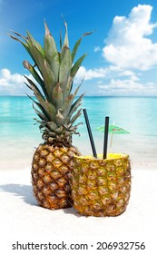 Pineapple cocktails on the sandy beach in the background the blue sea