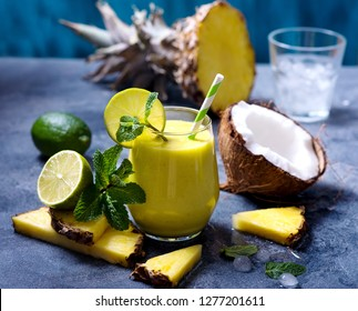 Pineapple, coconut cocktail, refreshing cold summer drink with ice, mint and lime, tropical fruit smoothie