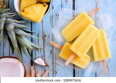 Pineapple coconut popsicles in a cluster. Top view scene over a blue wood background.