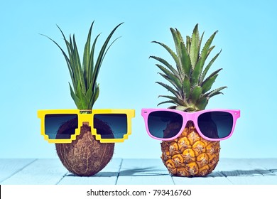 Pineapple Coconut tropical fruit fashion on Beach. Minimal concept. Bright summer vibes, hipster pineapple and coconut. Creative art concept. Summertime hot party, funny pineapple mood