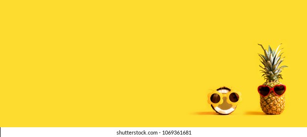 Pineapple and coconut wearing sunglasses on a yellow background