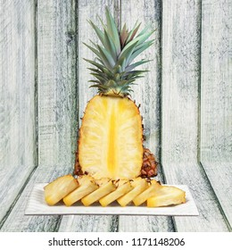 Pineapple cut wedges on the plate wooden background healthy snack.