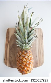 A pineapple in a flat lay layout on a wooden cutting board against a white background