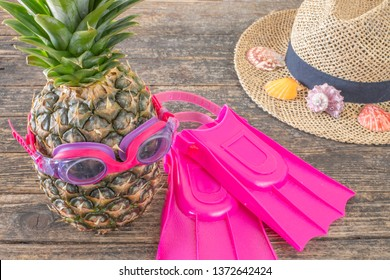 Pineapple with flippers and swimming glasses