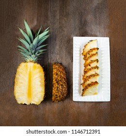 Pineapple fruit cut half, quarter and wedges and  displayed on white plate and wooden background. Square Composition. Juicy organically grown ripe and sweet