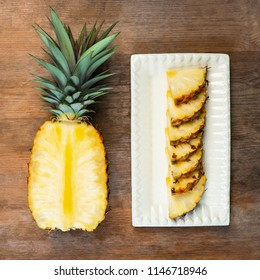 Pineapple fruit cut half and wedges and  displayed on white plate and wooden background. Square Composition. Juicy organically grown ripe and sweet